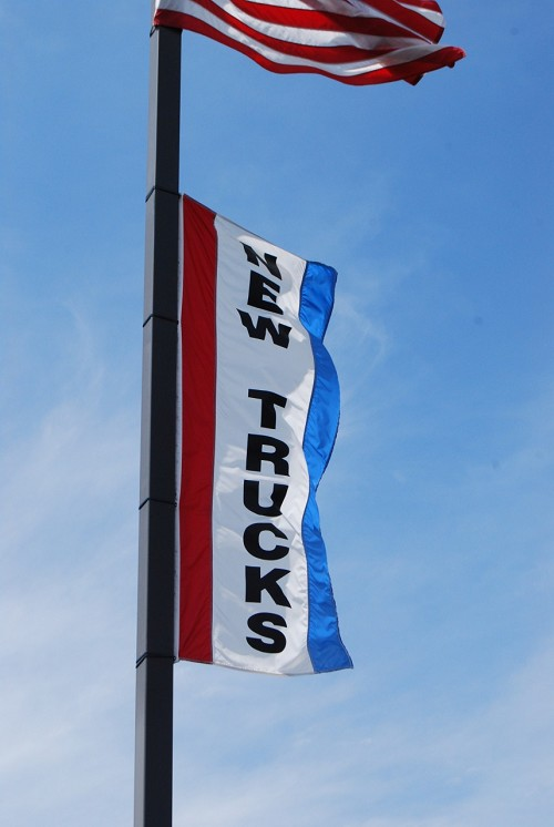3' x 8' Nylon Vertical Flags, shown in Red, White and Blue with New Trucks slogan.